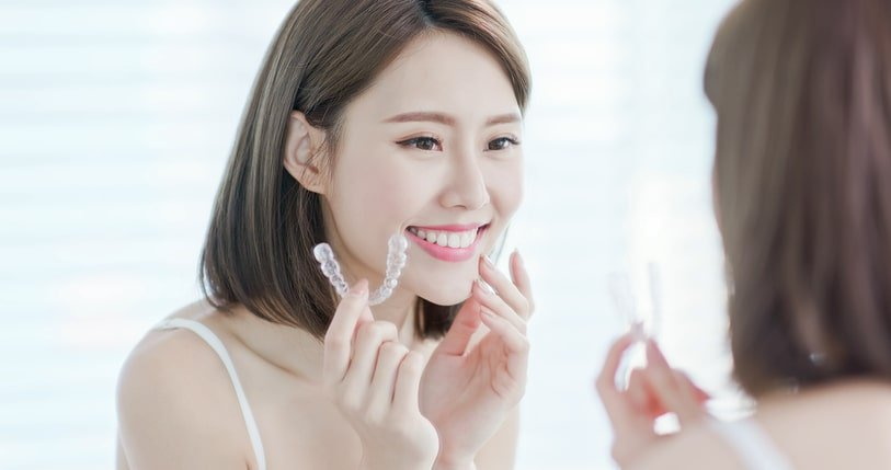 Lady having nice straight teeth after using Invisalign in Singapore